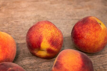 Ripe peaches on wooden background, close up