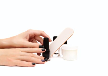 Female hands and manicure tools on white background Фото со стока