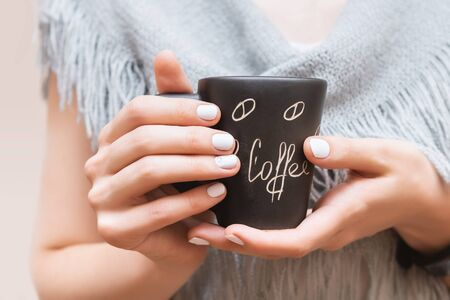 Female hands with white nail design holding black cup Фото со стока
