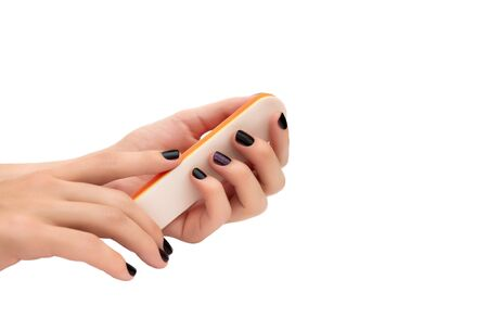 Female hands holding nail file on white background