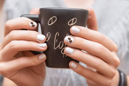 Female hands with white nail design holding black cup Reklamní fotografie