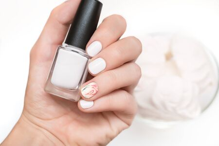 Female hand with white nail design holding nail polish bottle Фото со стока