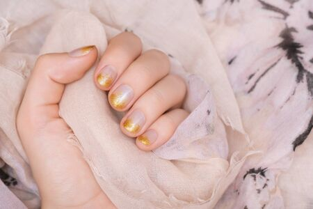 Female hand with gold glitter nail design