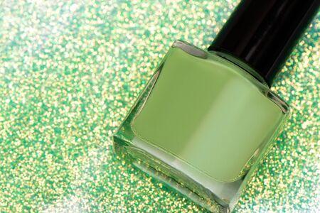 Bottle of green nail polish on glitter background