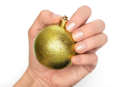 Female hand with glitter nail design holding christmas ball.