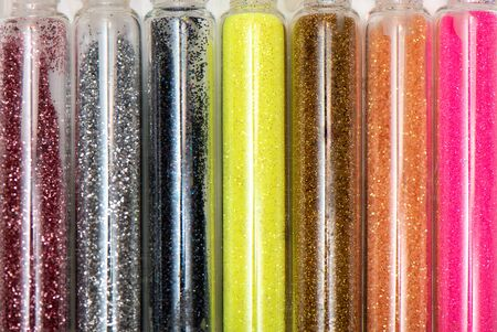 Different colored glitters in transparent glass jars.