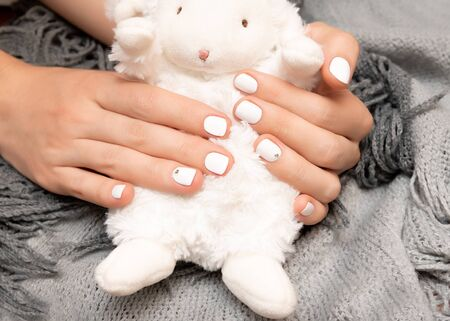 Female hand with white nail design holding soft toy sheep. Reklamní fotografie