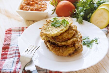 Squash fried fritters. Vegetable vegetarian food on white plate.