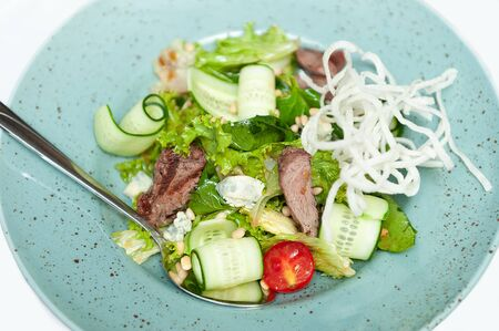 Beef salad with lettuce, cucumber and cheese.