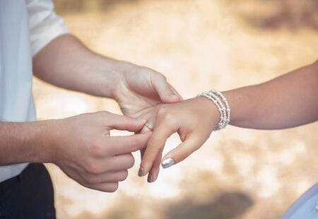 Couples hands with wedding rings on yellow nature background.