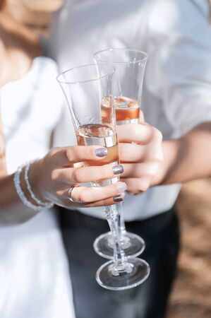 Wedding glasses with champagne in couples hands