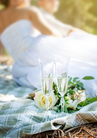 Wedding glasses with champagne and couple on background