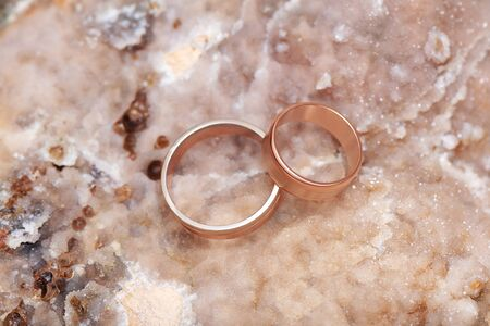 Wedding rings on a sparkle stone background.