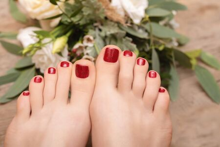 Beautiful female feet with red glitter pedicure.