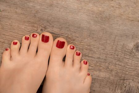 Beautiful female feet with red pedicure on wooden background.