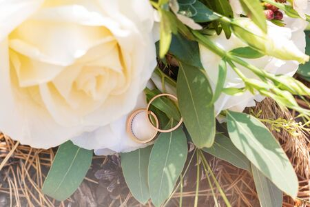 Wedding rings on a green spruce branch and flower bouquet.