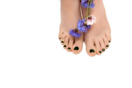 Female feet with green pedicure and flower on white background.