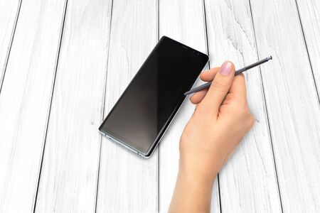 Female hands with cell phone with stylus on wooden background.