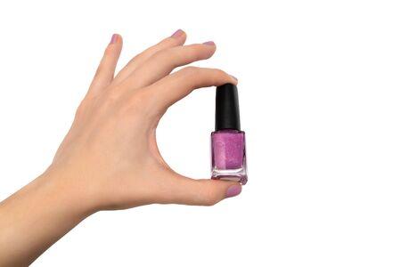 Female hand holding nail polish bottle on white background 写真素材