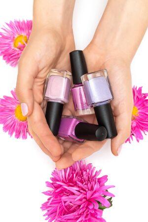 Female hands holding nail polish bottles on white background Reklamní fotografie