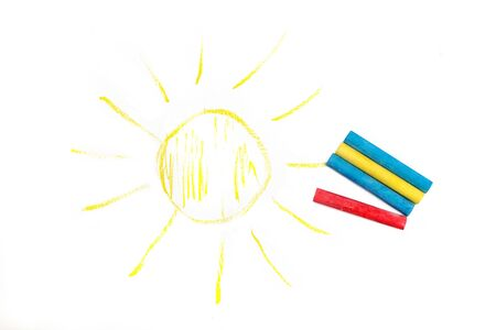 Colored crayons and painted sun on a white sheet of paper Reklamní fotografie