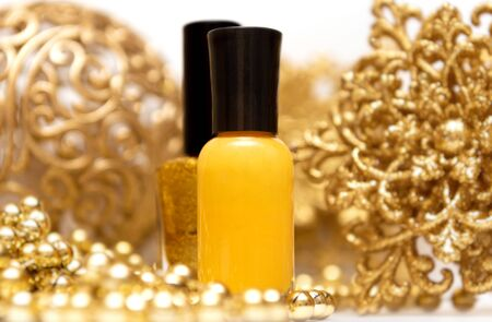 Yellow nail polish bottles with christmas decorations on background