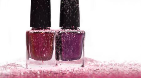 Group of nail polishes with glitter on white background.
