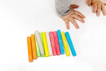 The childs hands are painted with colored crayons on a white sheet of paper Reklamní fotografie