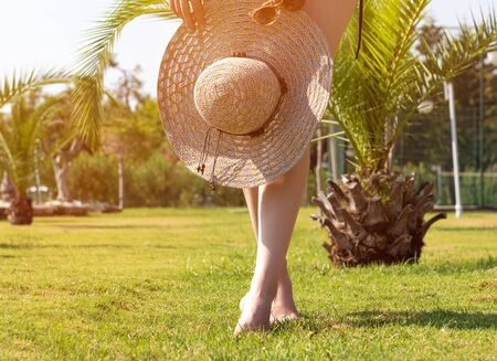 Young woman holding summer hat on green tropical background Reklamní fotografie
