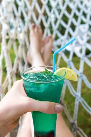 Refreshing coctail in female hand, vacation time