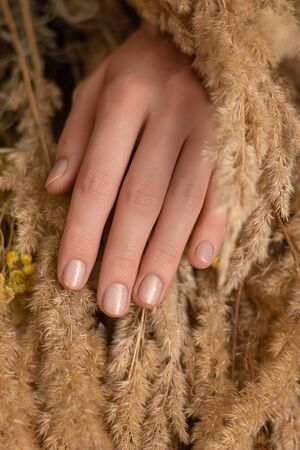 Female hand with nude glitter nail design.