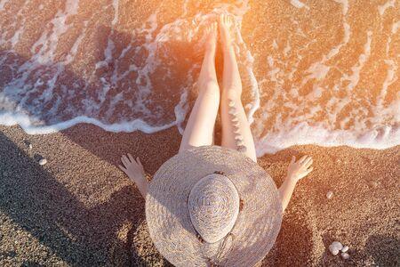 Woman wearing sun hat sitting by the seashore. Reklamní fotografie
