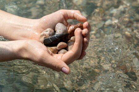 Sea pebbles in female hands and clear water on background.