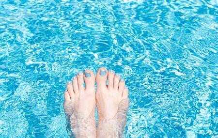 Female feet with glitter pedicure under clear pool water Reklamní fotografie
