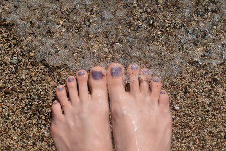 Female feet with glitter pedicure under clear water Reklamní fotografie