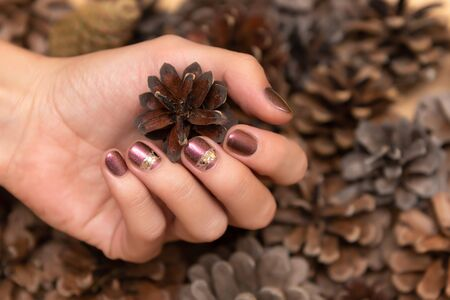 Female hand with brown glitter nail design holding pane cone. 写真素材 - 131688014
