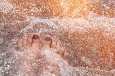 Female feet with glitter pedicure under clear water Stock Photo