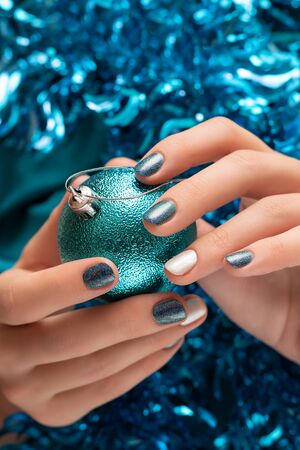 Beautiful female hand with blue christmas nail design. 写真素材