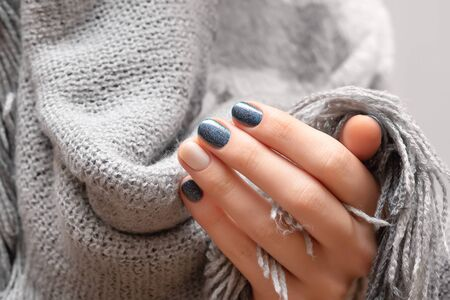 Female hands with blue glitter nail design