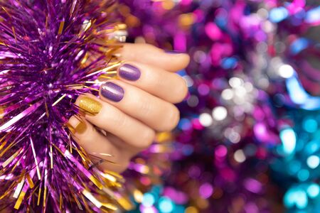 Beautiful female hand with purple christmas nail design.
