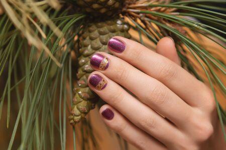 Female hand with purple glitter nail design holding pane cone. 写真素材