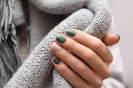 Female hand with green glitter nail design 写真素材