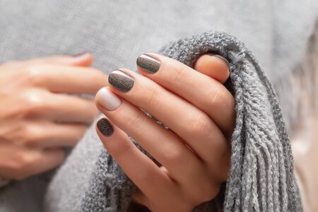 Female hands with brown glitter nail design