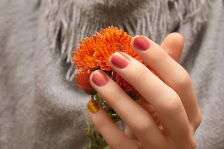 Female hand with glitter nail design holding flowers.