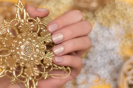Female hand with glitter nail design.