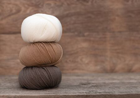 Close up of wool knitting on wooden background.