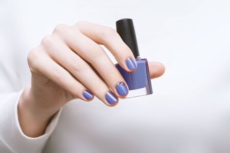 Female hand with purple nail design holding nail polish bottle. Stock Photo