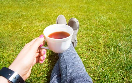 Female legs on green grass and cup of tea. Rest concept.
