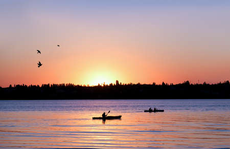Two kayaks on river at sunset. Boats saling on sunset