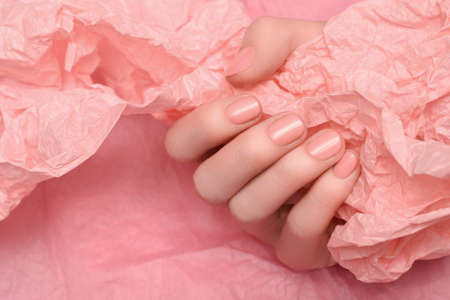 Female hand with pale pink nail design. Pale pink nail polish manicured hand. Female hands hold pale pink crumpled paper.